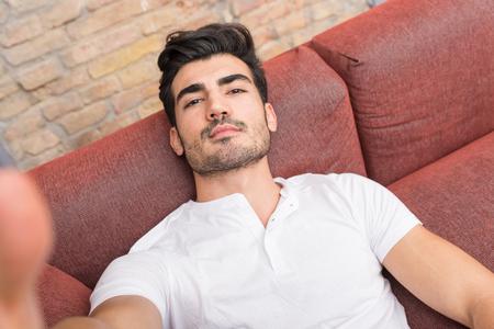 Porträt eines ernsten, gutaussehenden jungen Mannes, der ein Selfie spricht, während er auf einem Sofa in einem weißen T-Shirt aus der Perspektive des Smartphones sitzt.