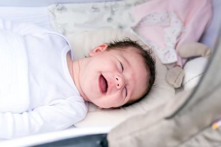 Porträt eines Babys, das an einem sonnigen Tag in einem Kinderwagen in einem Park liegt.
