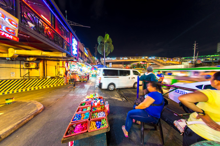 MANILA, PHILIPPINES - CIRCA MARCH 2018: View on daily life on the streets of the city as cars and pedestrians pass by during the night circa March, 2018 in Manila, Philippines.