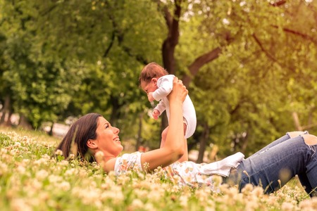 A young mother lying on the grass in the park while holding her baby in her arms.