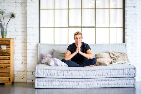 A young handsome man relaxing on the sofa in a loft style apartment