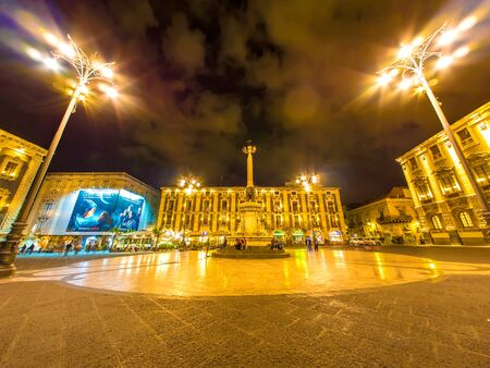 CATANIA, ITALY - CIRCA JUNE 2018: View on historic architecture of the main square as people pass by on the cobblestones streets at night circa June 2018 in Catania, Italy.