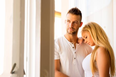 Beautiful young couple standing at the window