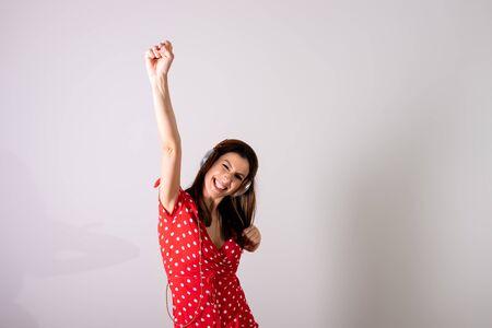 Een mooie jonge vrouw in een rode jurk die naar muziek luistert en danst voor een grijze achtergrond in een studio.
