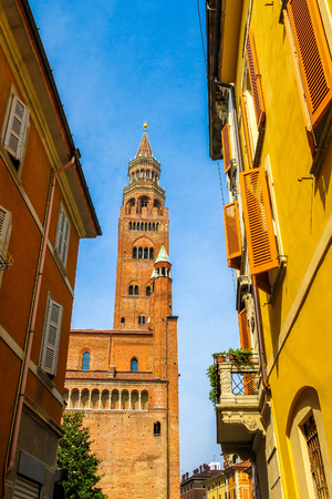 View on the famous Torrazzo bell tower with historic architectures in Cremona, Italy on a sunny day.
