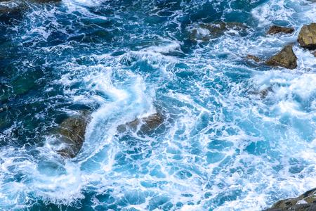 Rocks in the blue Mediterranean Sea on a bright sunny day.