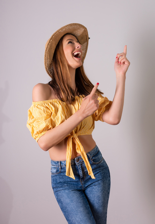 A happy young woman in a yellow dress pointing in front of a grey background in a studio.