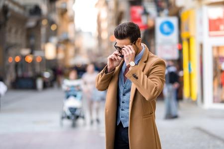 An elegant man walking and talking on his phone. Reklamní fotografie
