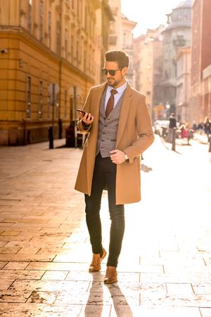 A handsome elegant man using his smartphone. Reklamní fotografie