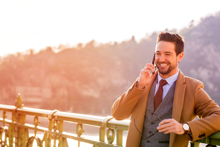An elegant man standing on a bridge and talking on his phone.