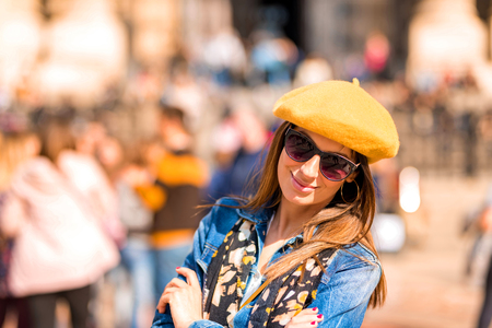 A beautiful young woman standing in the crowd in the center of a European city during spring.