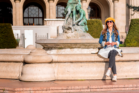 A beautiful young woman sitting at a fountain in the center of a European city during spring.