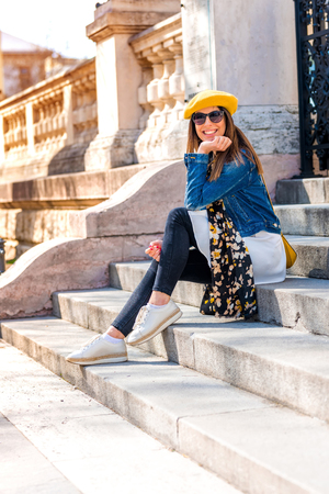 A beautiful woman sitting on the stairs of a European landmark.