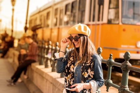 A beautiful woman enjoying a European city while a tram passes by. Reklamní fotografie