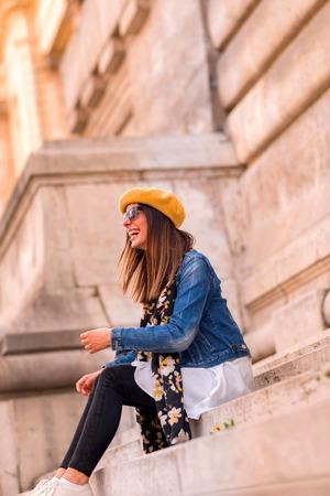 A beautiful woman sitting on the stairs of a mayor European landmark.
