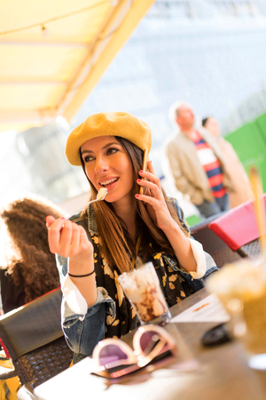 A beautiful young woman talking on a smartphone while having a ice coffee.