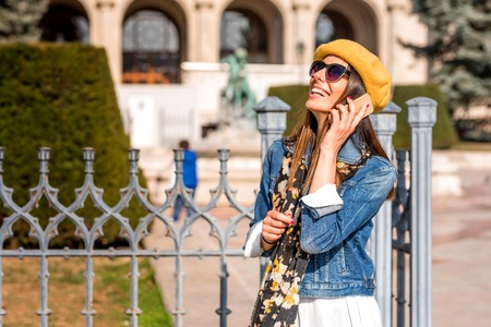 A beautiful woman talking on her phone during a sightseeing trip in a European city during spring.
