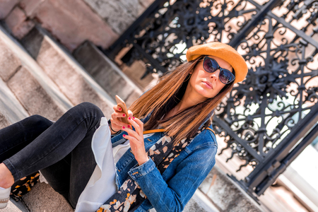 A beautiful woman using her smartphone in a European city during spring.