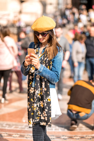 A beautiful woman using her smartphone in the pedestrian zone of a city during spring. Reklamní fotografie