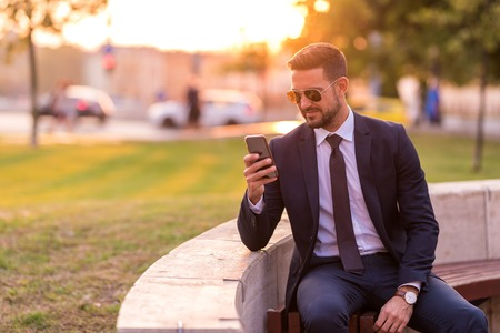 A handsome young businessman sitting on a bench and using his phone on a sunny day.