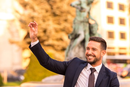A handsome young businessman sitting next to a fountain and waving on a sunny day.
