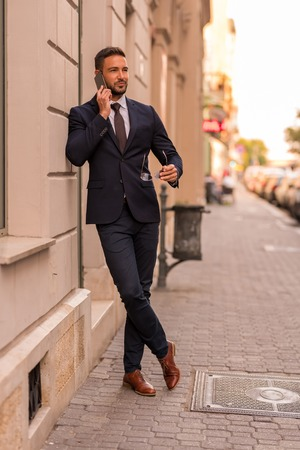 A handsome young businessman walking on the streets and talking on his phone on a sunny day. Reklamní fotografie