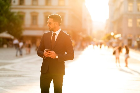 A handsome young businessman walking on the streets and using his smartphone on a sunny day.