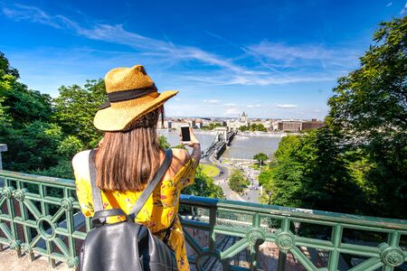 A young woman taking pictures of Budapest, Hungary with her phone.