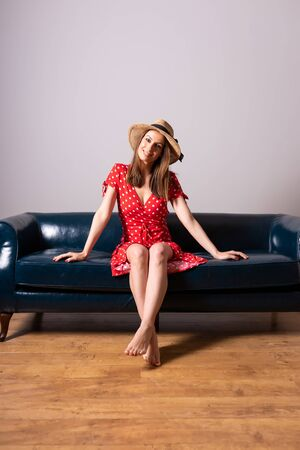 A beautiful young woman in a red dress sitting on a sofa.