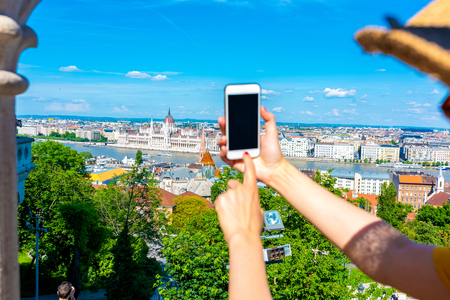 A young woman in the Castle of Budapest in Hungary taking pictures of the city with her phone. Reklamní fotografie