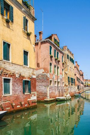 View on the historic architecture and the canal between the ancient buildings in Venice, Italy on a sunny day.