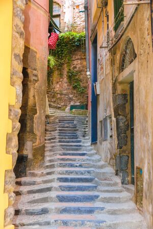 Old rock stairs between the colourful houses in Cinque Terry, Italy on a sunny day. Фото со стока