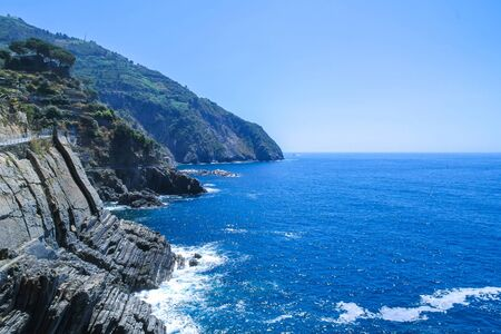 View over the blue Mediterranean Sea and the mountains of Cinque Terre, Italy on a sunny day with blue sky.