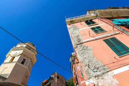 View over the the medieval clock tower of Cinque Terre, Italy with colourful houses on a sunny day.