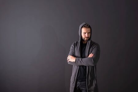 A serious handsome young man in a grey hoodie standing in front of a dark grey background in a studio.