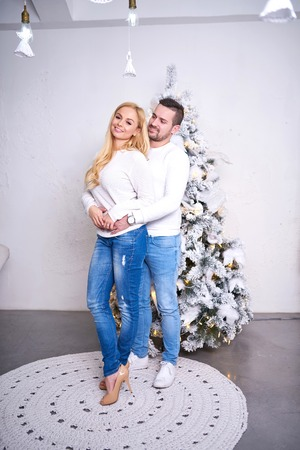 A beautiful happy young couple standing in front of the christmas tree and hugging each other.