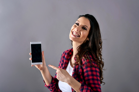 A young happy pregnant woman in a red shirt and a white tshirt showing her belly and a smartphone in front of a grey background in a studio.