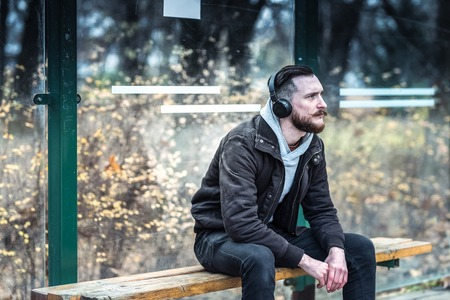 A handsome young hipster man waiting at the bus stop while listening to music on his headphones.