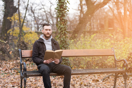A handsome young hipster man sitting on a bench and reading a book in the park.