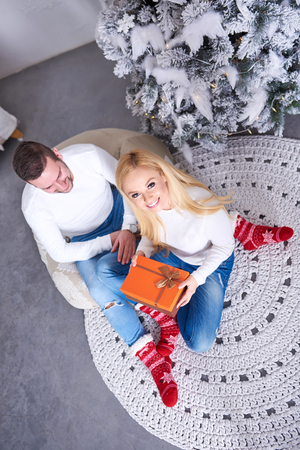 A beautiful happy young couple sitting on the ground with the christmas tree and giving presents to each other.