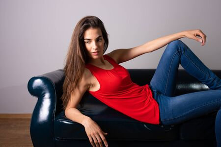 A beautiful smiling young woman in a red dress lying on a sofa.