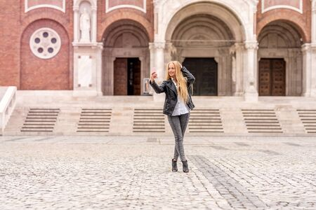 A beautiful woman in a leather jacket taking a selfie while standing on a square in front of a historic European church.