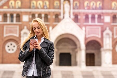 A beautiful woman in a leather jacket using her smartphone while standing on a square in front of a historic European church. Фото со стока