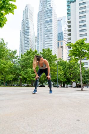An athletic woman in a grey top standing with her hands on her knees in the park with modern buildings in the background. Фото со стока - 134724997