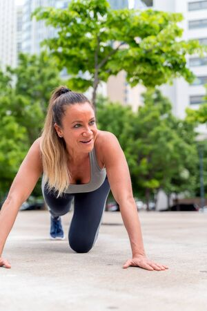 An athletic woman in a grey top doing pushups in the park with modern buildings in the background. Фото со стока