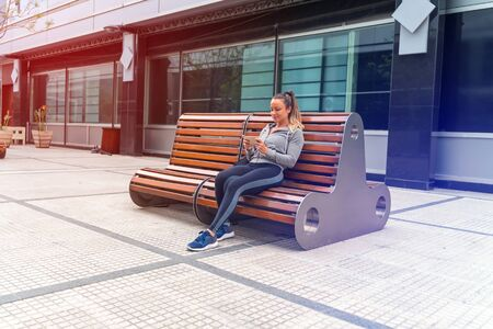 An athletic woman in a grey sweater and a black leggings sitting on a bench and using her smartphone. Фото со стока