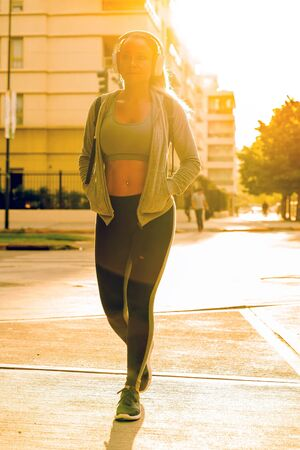 An athletic woman in a grey sweater walking on the street with the sunset in the background.