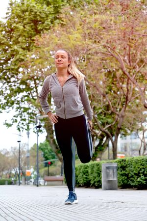 An athletic woman in a grey sweater and a black leggings standing in the park and stretching before the workout.