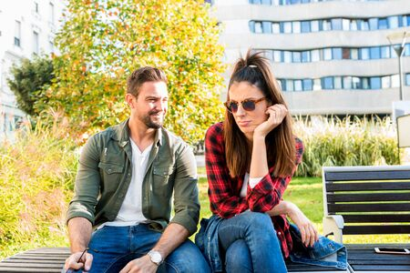 A girlfriend being annoyed by her boyfriend on a sunny day on a park bench..
