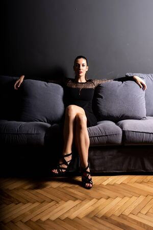 Strong portrait of a beautiful woman on the sofa..